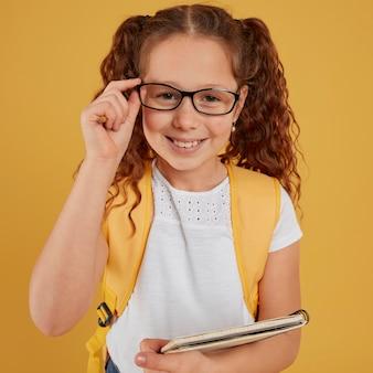 Criança segurando os óculos e um caderno