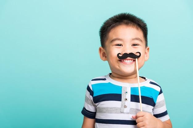 Criança segurando um adereço de bigode preto