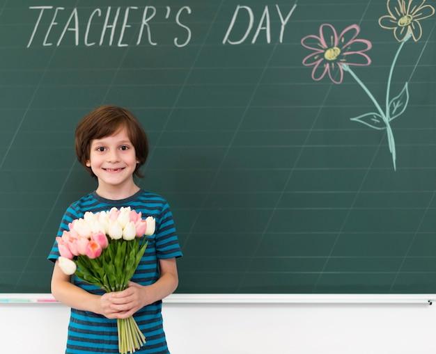 Criança segurando um buquê de flores ao lado de um quadro-negro