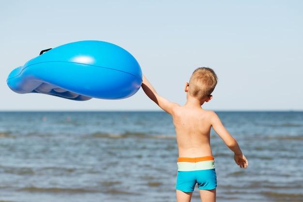Criança segurando um colchão inflável na praia em um dia quente de verão
