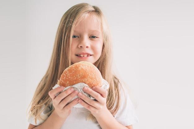 Criança segurando um pedaço de hambúrguer