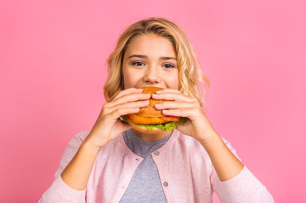 Criança segurando um pedaço de hambúrguer.