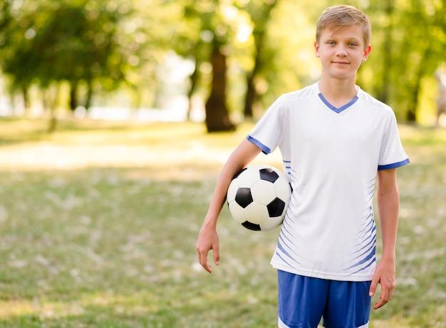 Criança segurando uma bola de futebol ao ar livre