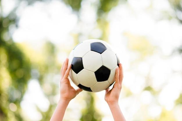 Criança segurando uma bola de futebol no ar