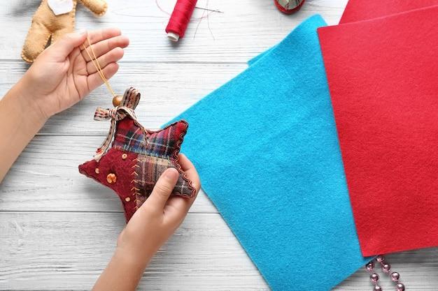 Criança segurando uma estrela de natal à mesa