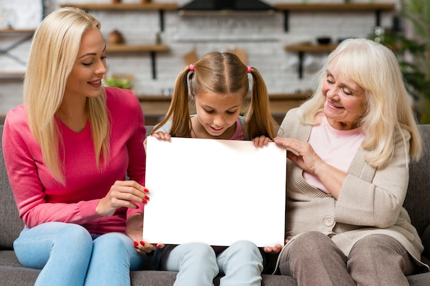 Criança segurando uma faixa vazia ao lado de mãe e avó