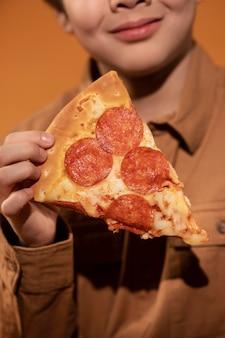 Criança segurando uma fatia de pizza