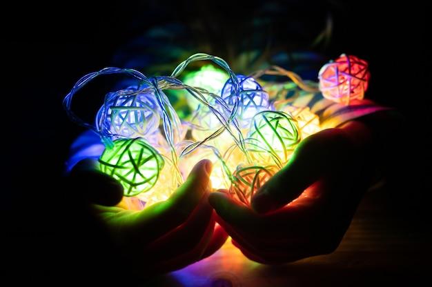 Criança segurando uma guirlanda nas mãos, brilhando com luzes coloridas multicoloridas à noite. aventura divertida e celebração de pessoas e crianças na véspera de natal ou feriado de ano novo