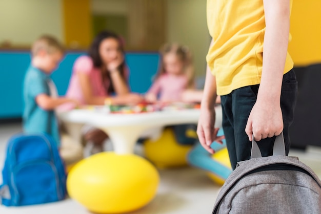 Criança segurando uma mochila com espaço de cópia