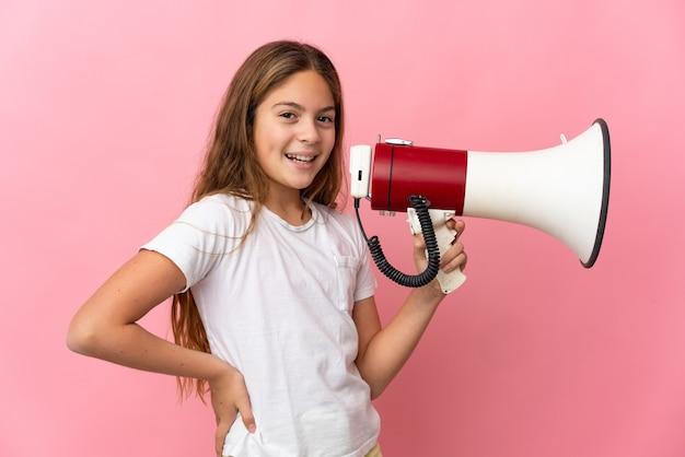Criança segurando uma parede rosa isolada segurando um megafone e sorrindo