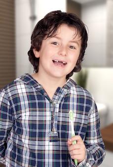 Criança sem alguns dentes escovando os dentes no banheiro