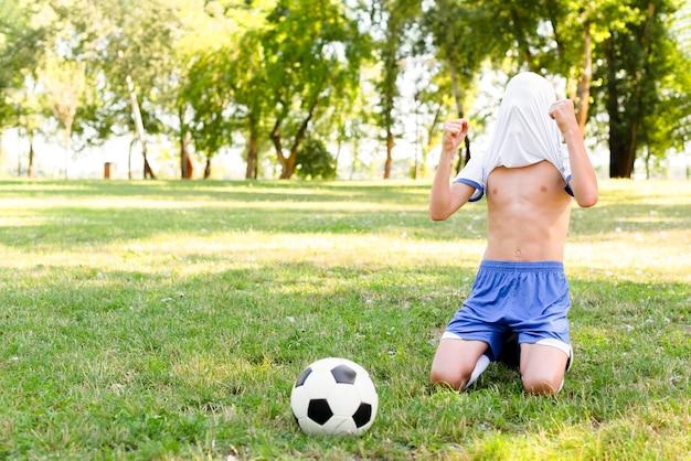 Criança sem camisa sendo vitoriosa após marcar um gol