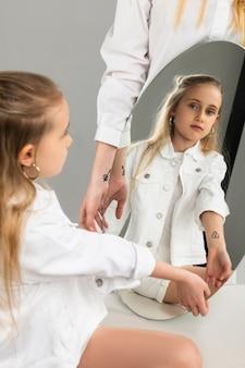 Criança sem emoção observando a foto na mão no reflexo do espelho