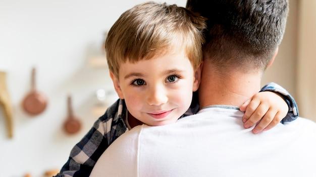 Criança sendo mantida pelo pai por cima do ombro