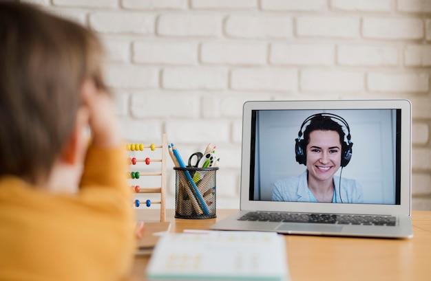 Criança sendo orientada em casa através da aula on-line