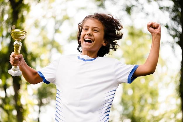 Criança sendo vitoriosa após uma partida de futebol