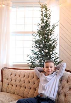 Criança senta no sofá no natal
