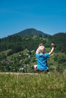 Criança senta-se nas montanhas com as mãos levantadas. fim de semana na natureza com crianças. quadro vertical