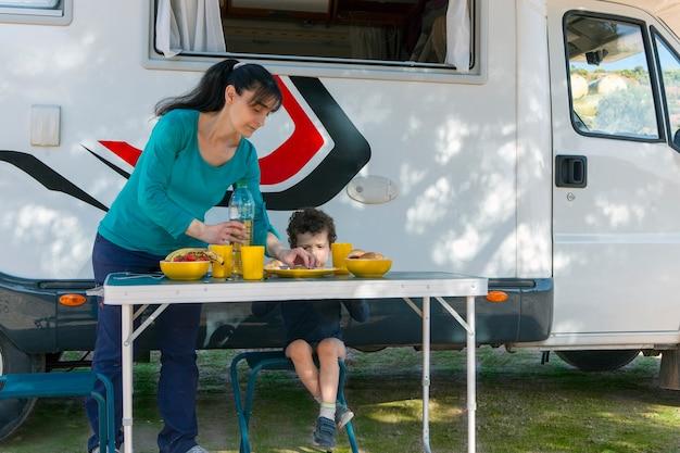 Criança sentada à mesa ao lado do trailer enquanto sua mãe serve sanduíches e bebidas