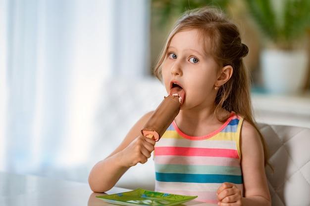 Criança sentada à mesa com sorvete na vara em esmalte de chocolate rosa de enchimento.