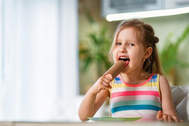 Criança sentada à mesa com sorvete no palito