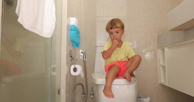 Criança sentada banheiro com olhar pensativo escolhe seu nariz