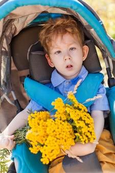 Criança sentada em uma cadeira de rodas está desfrutando de atividades no parque como outras pessoas. conceito de criança com deficiência feliz