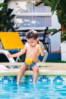 Criança sentada na beira de uma piscina com um copo de suco de laranja entre as pernas