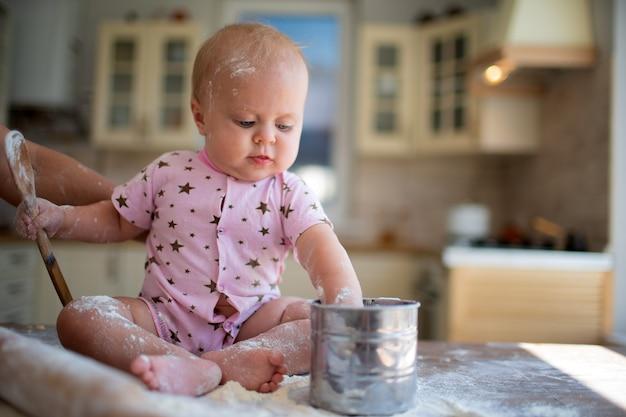 Criança sentada na cozinha com farinha em casa