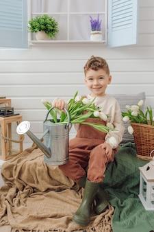 Criança sentada na varanda de um regador de casa de campo e buquê de flores tulipas botas de borracha natureza primavera tempo para a família