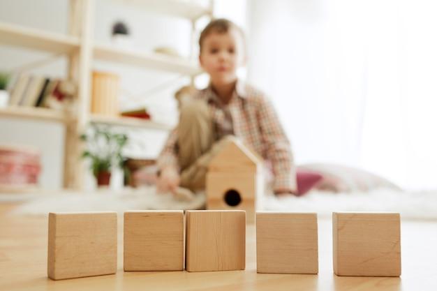 Criança sentada no chão. menino bonito brincando com cubos de madeira em casa.