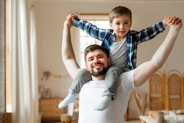 Criança sentada nos ombros do pai