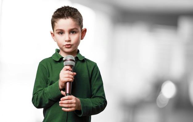 Criança séria com um microfone