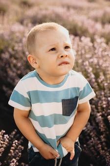 Criança séria e caucasiana olhando para cima e tocando sua camiseta em um campo de lavanda