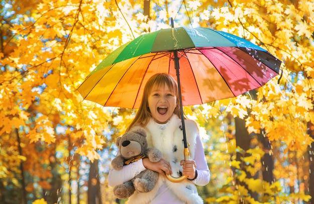 Criança sob um guarda-chuva no parque outono. foco seletivo.