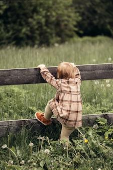 Criança sobe a cerca no jardim