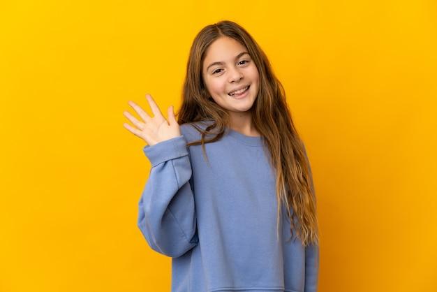 Criança sobre fundo amarelo isolado saudando com a mão com expressão feliz