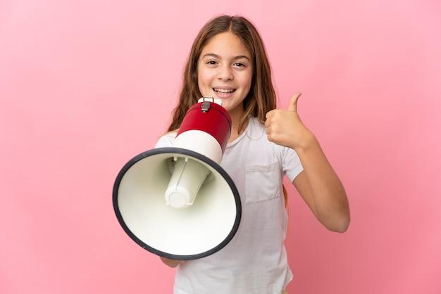 Criança sobre fundo rosa isolado gritando em um megafone para anunciar algo e com o polegar para cima