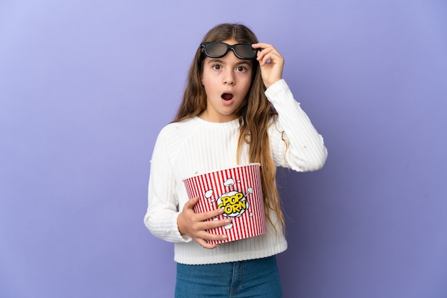 Criança sobre fundo roxo isolado surpreendida com óculos 3d e segurando um grande balde de pipocas