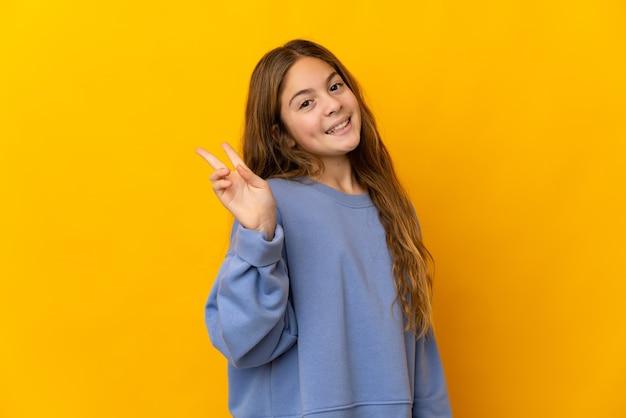 Criança sobre o amarelo isolado sorrindo e mostrando sinal de vitória