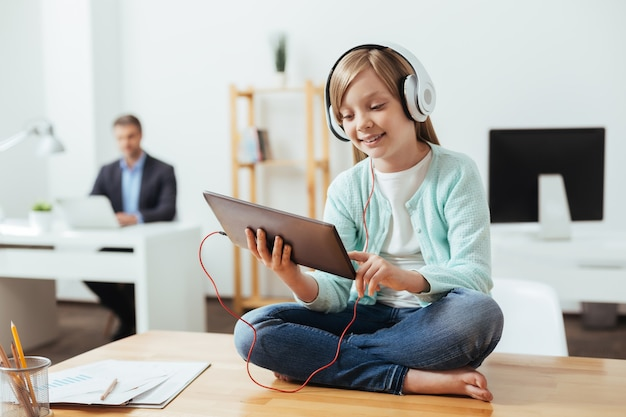 Criança sociável, animada e diligente, usando seu gadget enquanto usava fones de ouvido e se sentava na mesa do escritório do pai