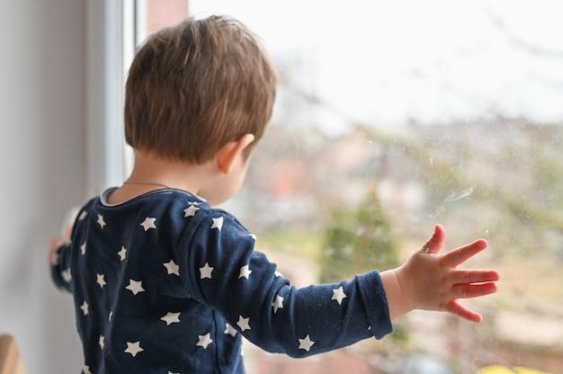 Criança solitária pela janela