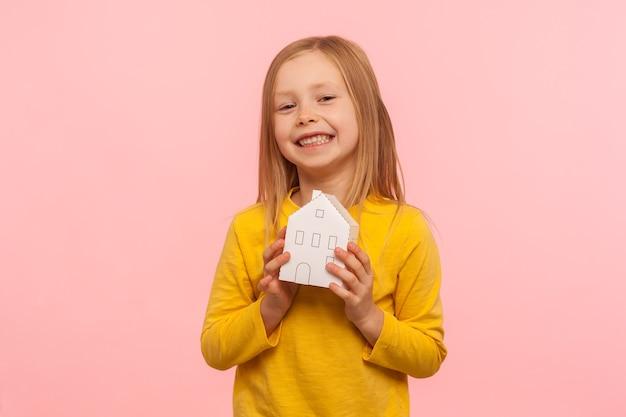 Criança sonhando com casa. retrato de feliz menina bonitinha segurando a casa de papel e sorrindo para a câmera, anúncio de agência imobiliária de confiança. foto de estúdio interno isolada em fundo rosa