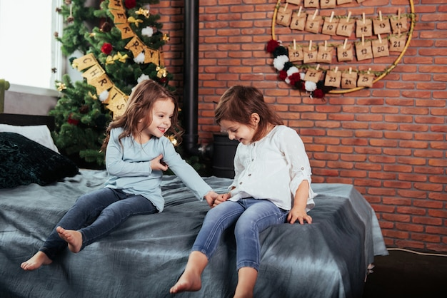 Criança sorri. crianças senta-se na cama com fundo decorativo. concepção de ano novo