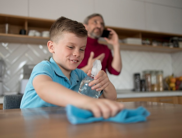 Criança sorridente a limpar mesa média