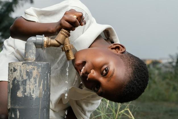 Criança sorridente africana bebendo água