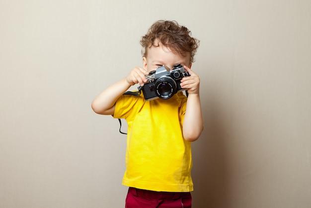 Criança sorridente alegre segurando uma câmera instantânea