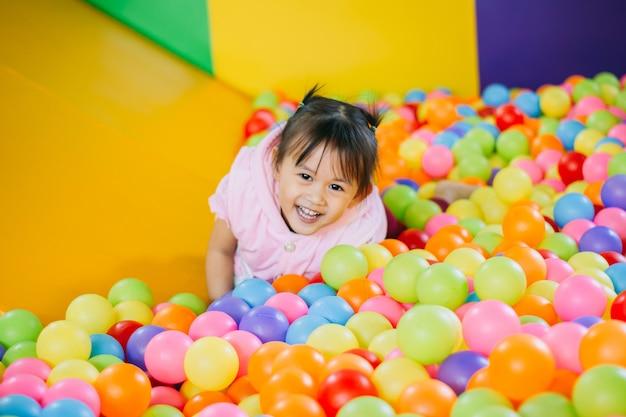 Criança sorridente brincando na piscina de bolas coloridas.