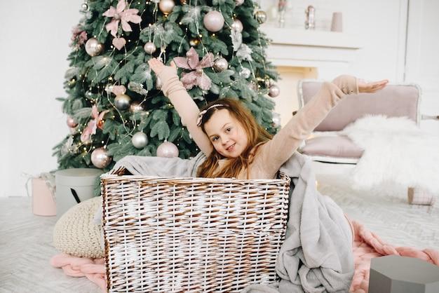 Criança sorridente caucasiana sentada em uma cesta perto da árvore de natal decorada