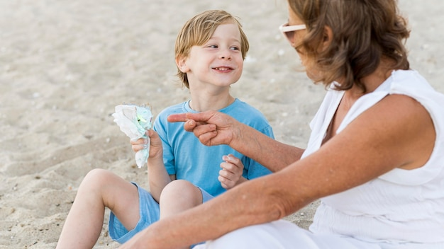 Criança sorridente com a avó na praia